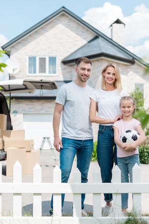 Vue de face de la famille heureuse avec petite fille tenant un ballon de football en face de la nouvelle maison
