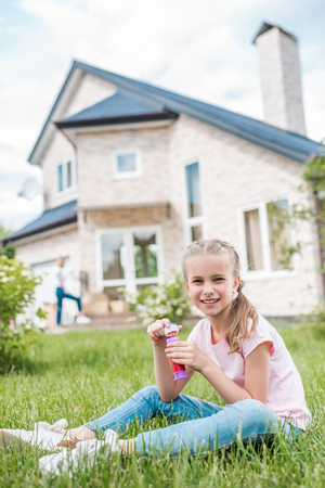 adorable little child with soap bubbles sitting on lawn while her mother standing behind in front of house