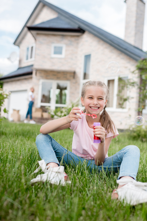 smiling little child with soap bubbles sitting on lawn while her mother standing behind in front of house