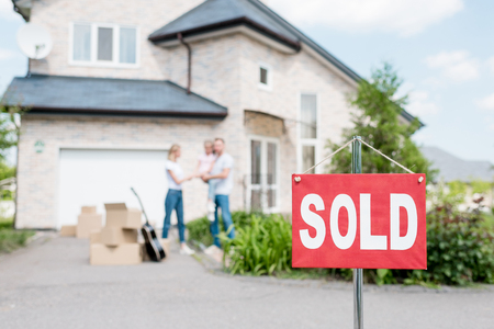 closeup view of for sold sign and family with child standing behind in front of house Stockfoto