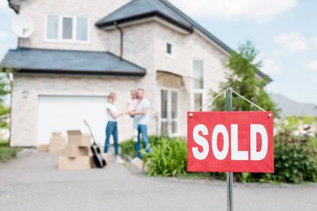 Nahaufnahme von für verkauftes Zeichen und Familie mit Kind, das hinter vor Haus steht Standard-Bild
