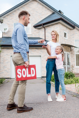 real estate agent with sold sign giving key to young woman with daughter in front of new house