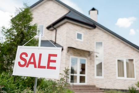 Immagine ravvicinata di cartello in legno con segno di vendita davanti al cottage moderno