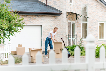 woman unpacking cardboard boxes near guitar in front of new house Stockfoto