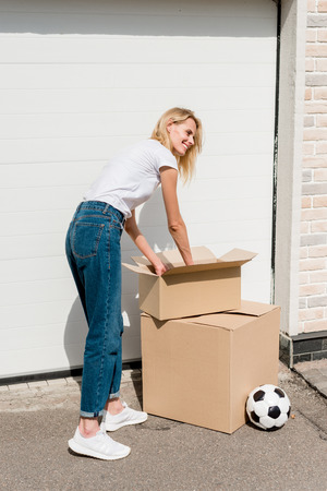 young woman unpacking cardboard boxes near soccer ball in front of garage of new house