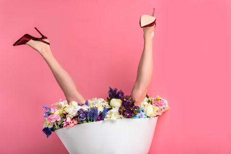upside down of female legs in high heeled shoes and skirt with beautiful flowers isolated on pink Stockfoto
