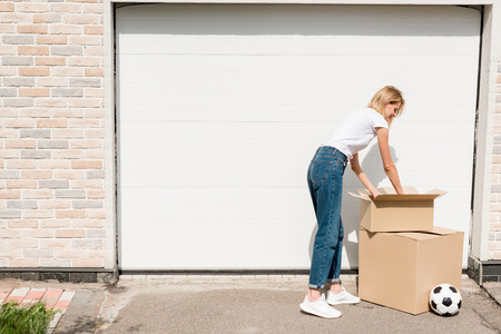 smiling young woman unpacking cardboard boxes near soccer ball in front of garage of new house