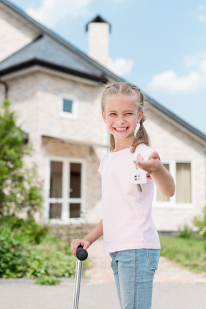 happy child with on kick scooter holding key with trinket near new house