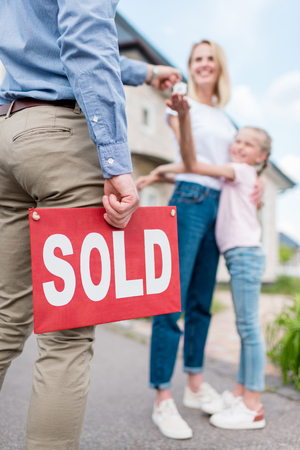 cropped image of realtor with sold sign giving key to young woman with daughter in front of new house