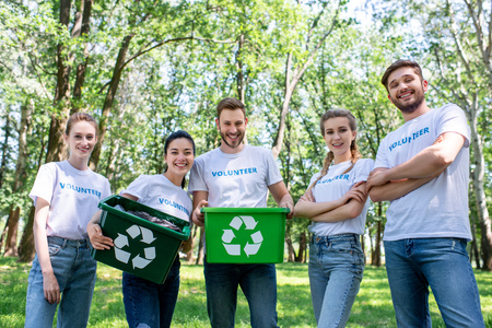 young volunteers with green recycling boxes after cleaning park Фото со стока - 106886382