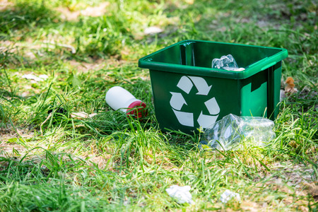 Recyclingbox und Plastikmüll auf grünem Gras