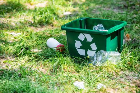 scatola di riciclaggio e rifiuti di plastica sull'erba verde