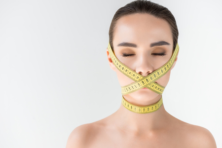 attractive young woman with closed mouth by measurement tape isolated on gray background Stockfoto