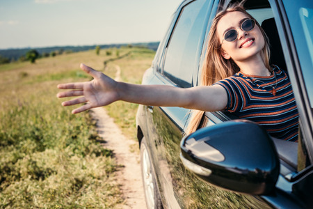 stylish woman in sunglasses leaning out hand from car window