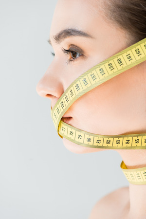side view of attractive young woman with closed mouth by measurement tape isolated on gray background Archivio Fotografico - 106017735