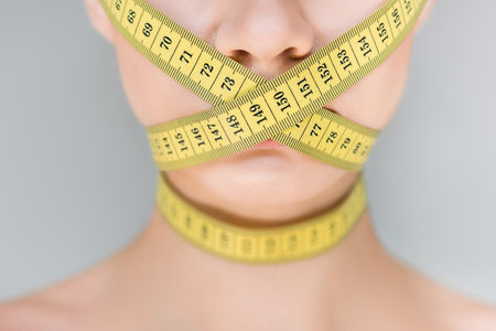 cropped image of woman with closed mouth by measurement tape isolated on gray background Archivio Fotografico - 106017842