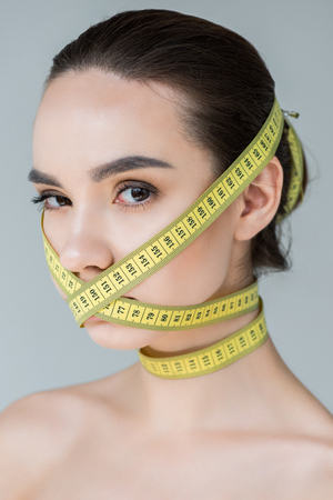 portrait of attractive young woman with closed mouth by measurement tape isolated on gray background Archivio Fotografico - 106018043