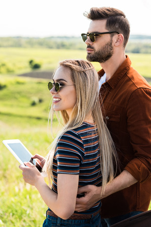 young stylish couple in sunglasses standing with digital tablet Stock Photo
