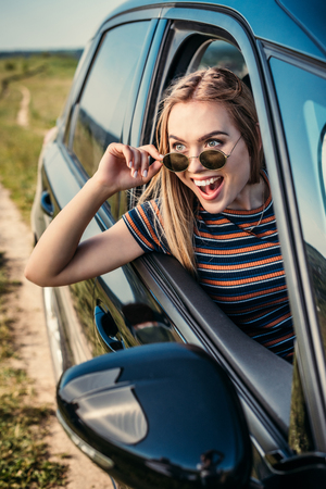 front view of excited young woman leaning out from car window