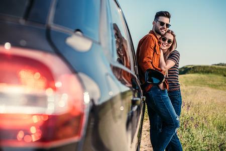 glückliches stilvolles Paar in der Sonnenbrille, die nahe Auto auf ländlicher Wiese steht Standard-Bild