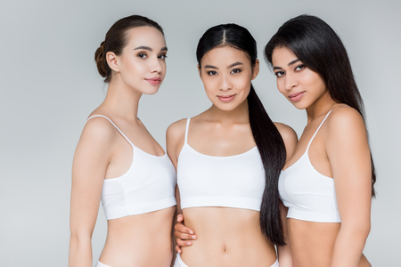 three attractive multiethnic women looking at camera isolated on gray background