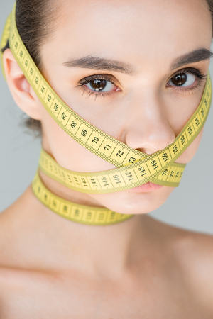 portrait of attractive young woman with closed mouth by measurement tape isolated on gray background