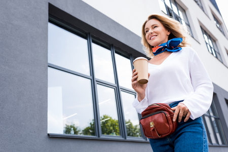 low angle view of attractive woman walking with disposable coffee cup on street Reklamní fotografie