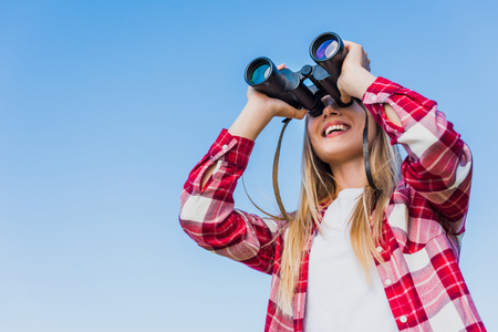 low angle view of female traveler looking through binoculars against blue sky