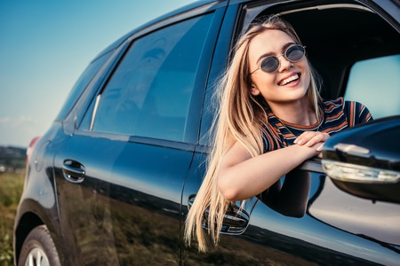 happy stylish woman in sunglasses leaning out from car window