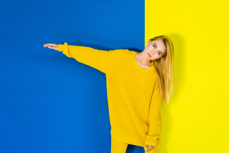 Attractive young girl posing in yellow clothes on blue and yellow background 写真素材