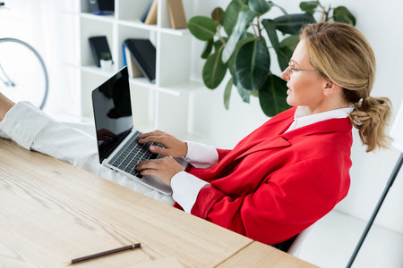 attractive businesswoman working with laptop and legs on table in office Stock Photo