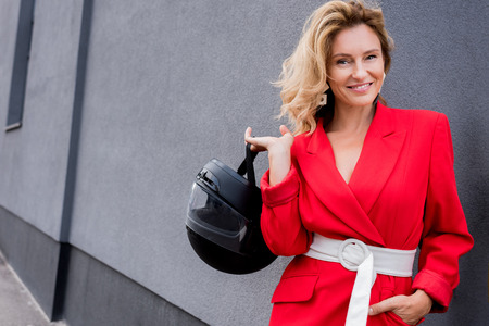 smiling attractive woman in red jacket holding motorcycle helmet on street