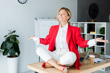 happy attractive businesswoman meditating in lotus pose on table in office Stock Photo