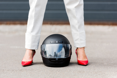 cropped image of woman in red shoes standing near motorcycle helmet on street