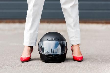 immagine ritagliata della donna in scarpe rosse in piedi vicino al casco del motociclo sulla strada