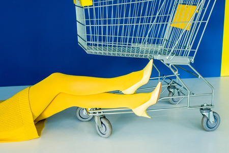 Cropped view of female legs in yellow shoes by shopping cart on blue background