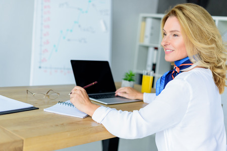 smiling attractive businesswoman sitting at table with laptop in office