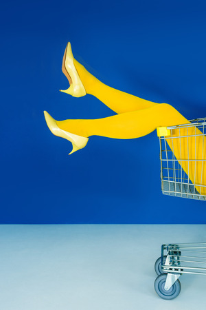 Cropped view of female legs in shopping cart on blue background