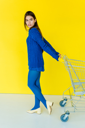 Beautiful brunette girl in blue clothes pulling shopping cart on yellow background Stockfoto