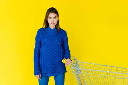 Female fashion model in blue sweater holding shopping cart isolated on yellow background