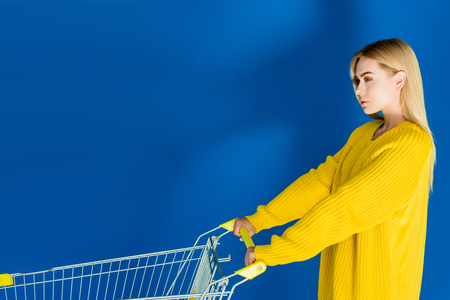 Attractive young girl pushing shopping cart on blue background