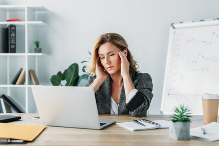 attractive businesswoman having headache and looking at laptop in office Stock Photo