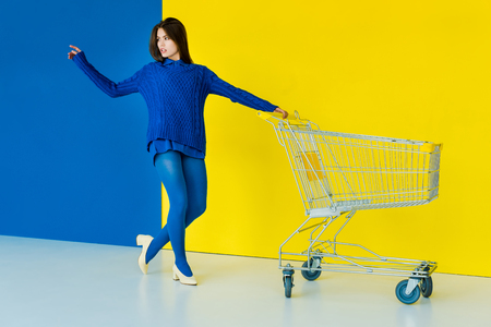 Elegant brunette woman in blue sweater posing by shopping cart on blue and yellow background