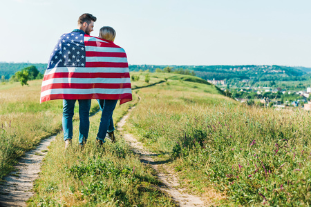 rear view of young couple with american flag on rural meadow, independence day concept