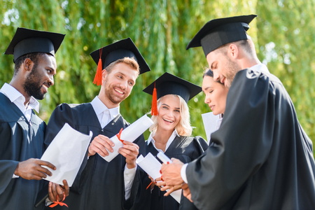 happy young graduated students in capes with diplomas Stock Photo