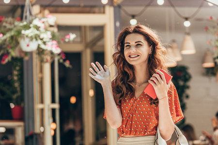 portrait of cheerful woman with smartphone in hand waiving to someone on street