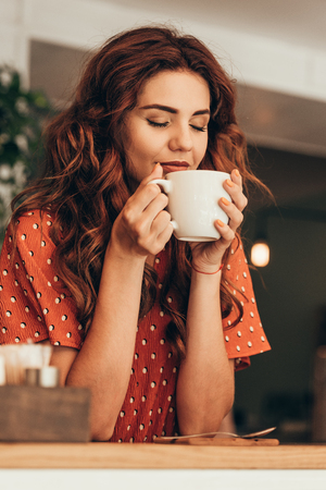 portrait of beautiful woman with eye closed holding cup of aromatic coffee in hands in cafe