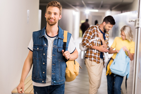 happy handsome student walking by college corridor 写真素材