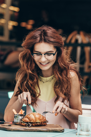 portrait of smiling woman in eyeglasses having breakfast alone in cafe