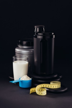 protein shaker with glass of white liquid and measuring tape isolated on black